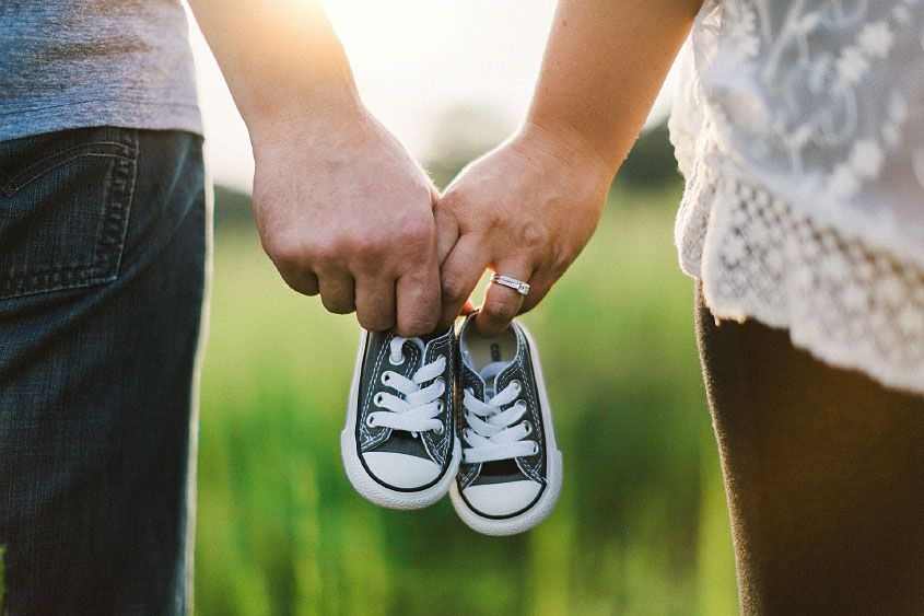 couple holding hands and baby shoes 2